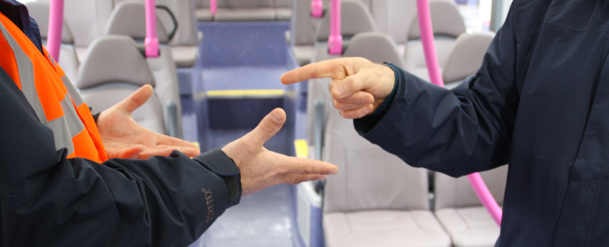 Man pointing finger at another man who has both his hands open signalling non-aggression